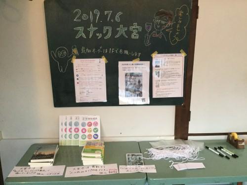 美智乃さんが作ってくれた専用ボードの前で著作を売らせてもらいました。ネームタグは常連客の多田さんが寄付してくれたものを使っています